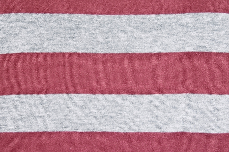 Knitted red-gray striped fabric texture background