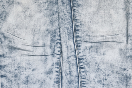 Acid washed jeans with folds on a lap of denim