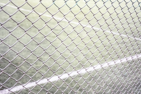 Tennis court fencing with netting netting against the background of the court and marking with white paint sports texture