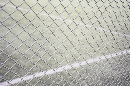 Tennis court fencing with netting netting against the background of the court and marking with white paint sports texture overlay texture Фото со стока