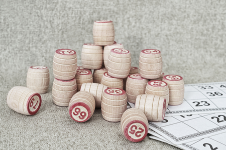 Lotto game with wooden barrels and cards with numbers on canvas background - simple still life in rustic style