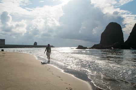 left behind: Woman walks across the beach Stock Photo