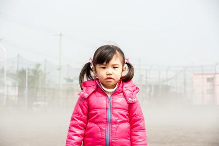 Mädchen stehen im Nebel.