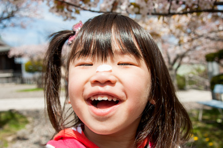 child laughing: Girl with cherry blossom petals in the nose Stock Photo