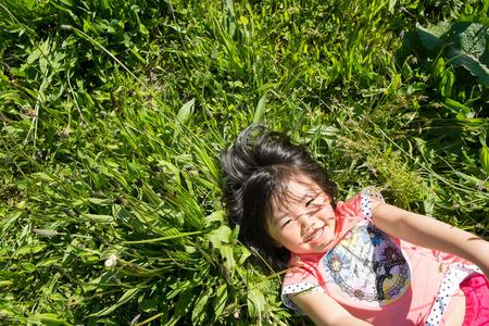 lie down: Girls lie down in the grass.