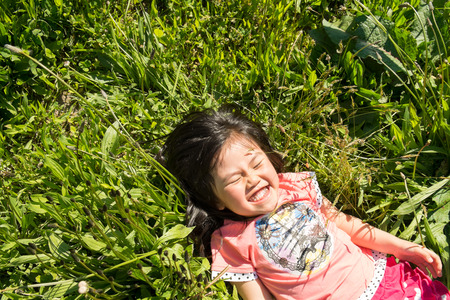 close your eyes: Girls lie down in the grass.
