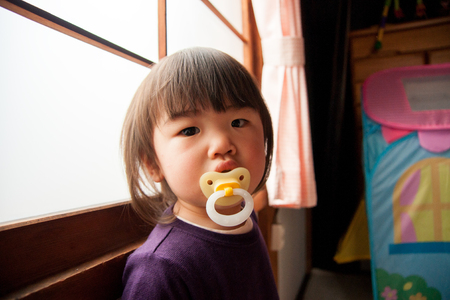 window treatments: Pacifiers mouth girl was Stock Photo