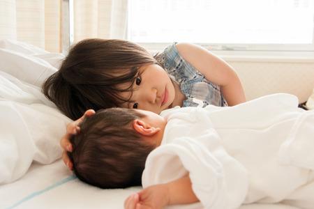 子供が赤ちゃんの頭を撫でください。
