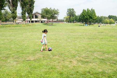 futbol infantil: Ni�a jugando con un bal�n de f�tbol Foto de archivo