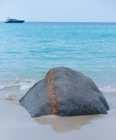 Stone on the sand and a beautiful yacht in the sea