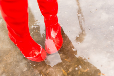 Feet in red rubber boots in the spring pool Stock Photo