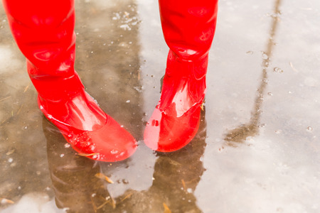 Feet in red rubber boots in a puddle Stock Photo