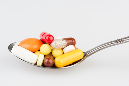 Pills in metal teaspoon on the grey medical table Stock Photo