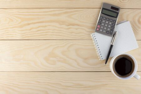 sign equals: Calculator,  spiral note pad, coffee and pen on wood background