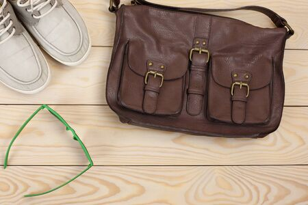 leather bag: Different objects on wooden background: leather bag, glasses, gumshoes