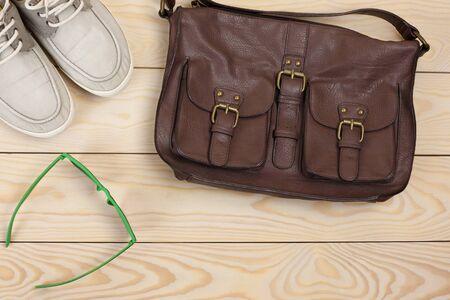 leren tas: Verschillende objecten op houten achtergrond: lederen tas, bril, gumshoes