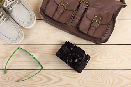 leather bag: Outfit of traveler, student, teenager, young man. Different objects on wooden background: leather bag, camera, glasses, gumshoes Stock Photo
