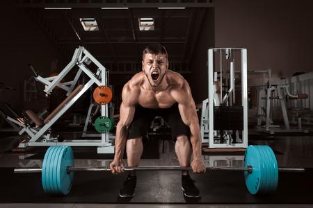 cuclillas: Hombres musculosos elevaci�n Peso Muerto En El Gimnasio Foto de archivo