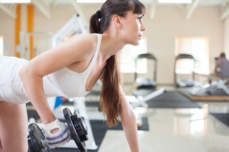 Female fitness girl exercising indoor in fitness center. photo