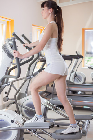 exercice: woman with elliptical cross trainer in sport fitness gym club Stock Photo