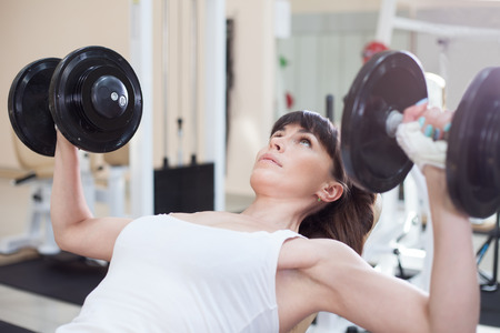 levantando pesas: Mujer levantando pesas y trabajar en el pecho en el gimnasio Foto de archivo
