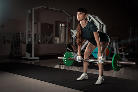 crouches: beautiful sports fitness girl with a barbell in the gym Stock Photo