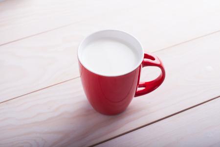 mleka: czerwony kubek mleka na drewnianym stole