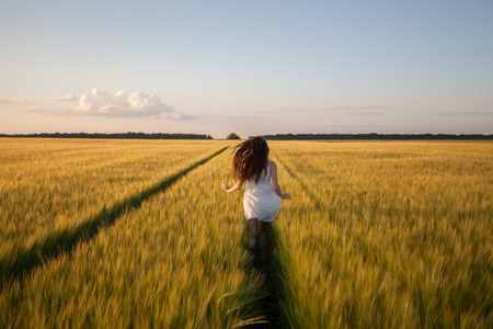 run woman: beautiful woman run away in yellow wheat field Stock Photo
