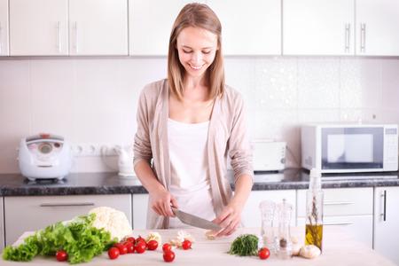 kitchen knife: Mujer joven que cocina en la cocina. Concepto de dieta vegetariana. Estilo De Vida Saludable. Cocinar en casa. Preparar Comida