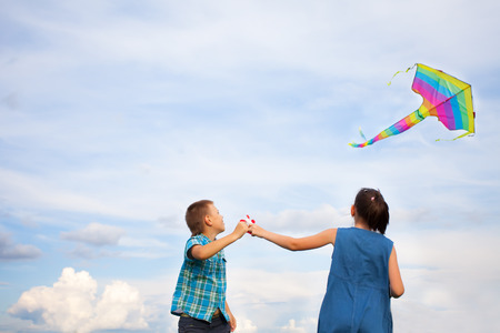 wind up: boy and girl flying  kite on a bright summers day.