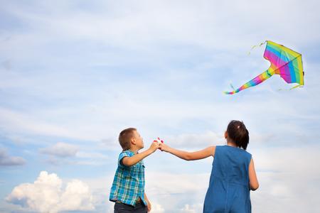papalote: chico y chica volando cometa en un d�a de verano brillante.