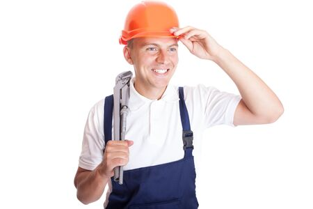 Smiling handsome handyman in work clothes with tool Stock Photo