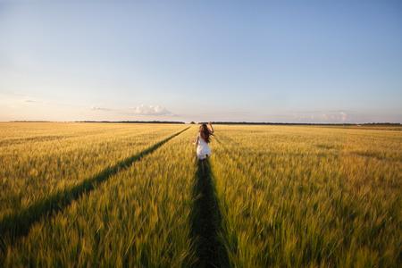 woman posing: beautiful woman run away in yellow wheat field Stock Photo