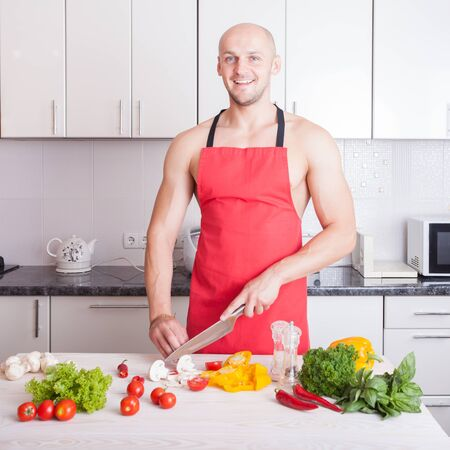 muscle guy: muscle man cooking in the kitchen, healthy food,  healthy lifestyle