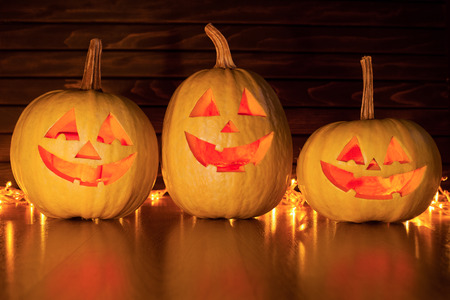 Scary Halloween pumpkins with eyes glowing inside on wooden background