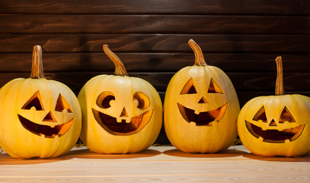 Scary Halloween pumpkins on wooden background