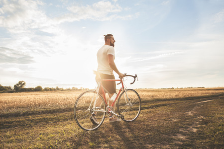 active lifestyle: Young hipster man with bicycle into the sunset