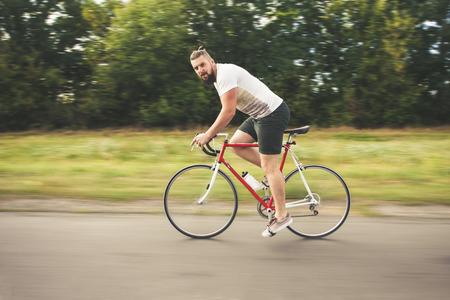 bicyclette: Jeune hippie barbu conduite bicyclette rapide sur la route Banque d'images