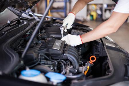 mecanico automotriz: Manos del mec�nico de autom�viles en el servicio de reparaci�n de autom�viles. Foto de archivo
