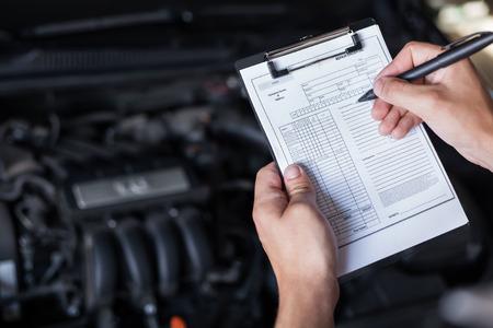 the clipboard: Reparador del mecánico del primer coche de la inspección