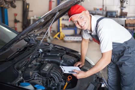 Portrait eines Mechanikers Notizen und lächelnd
