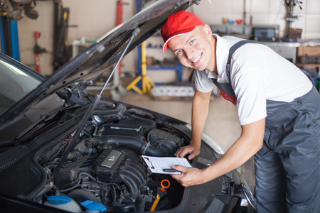 body check: Portrait of a mechanic taking notes and smiling