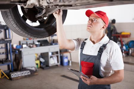 car shop: Portrait of a mechanic taking notes under a car