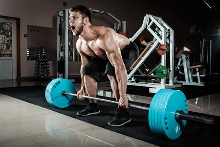 man power: Muscular Man Doing Heavy Deadlift Exercise Stock Photo