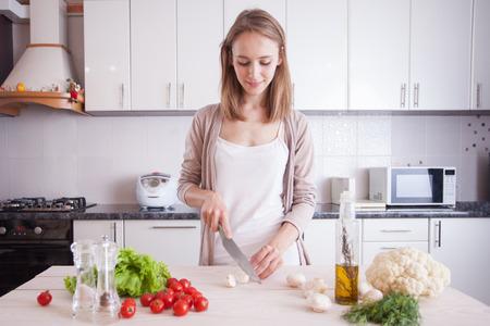 ライフスタイル: 若い女性は、台所で料理。菜食主義の概念をダイエットします。健康的なライフ スタイル。自宅で料理。食品を準備します。