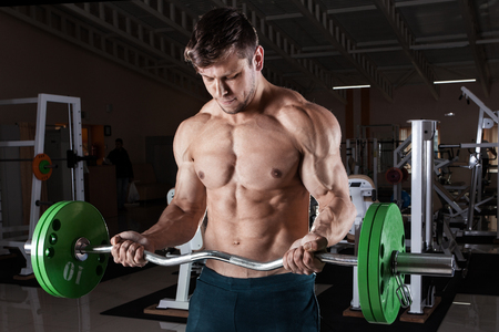 Man at the gym. Man makes exercises with barbell Stock Photo