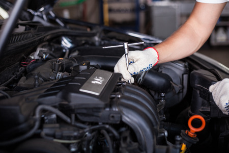 maintenance engineer: Hands of car mechanic in auto repair service.