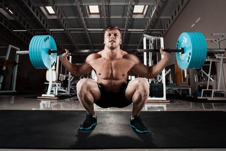 en cuclillas: El hombre en el gimnasio. Ejecutar el ejercicio en cuclillas con el peso, en el gimnasio