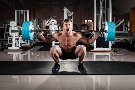 cuclillas: El hombre en el gimnasio. Ejecutar el ejercicio en cuclillas con el peso, en el gimnasio