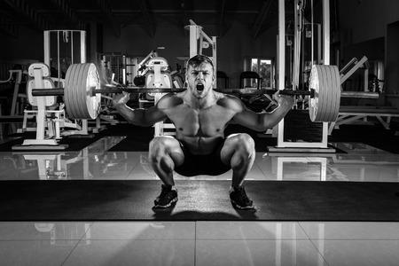 gimnasio: El hombre en el gimnasio. Ejecutar el ejercicio en cuclillas con el peso, en el gimnasio